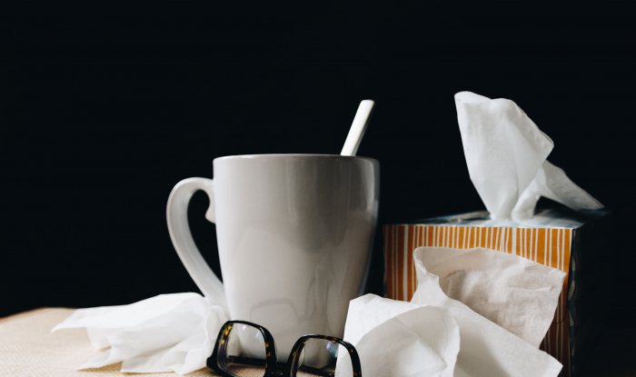 Picture of a hot drink and box of tissues on a desk